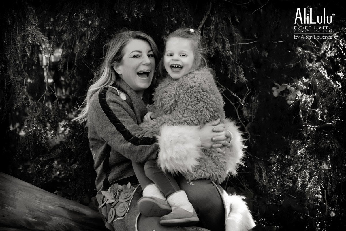 mummy and daughter laughing in park