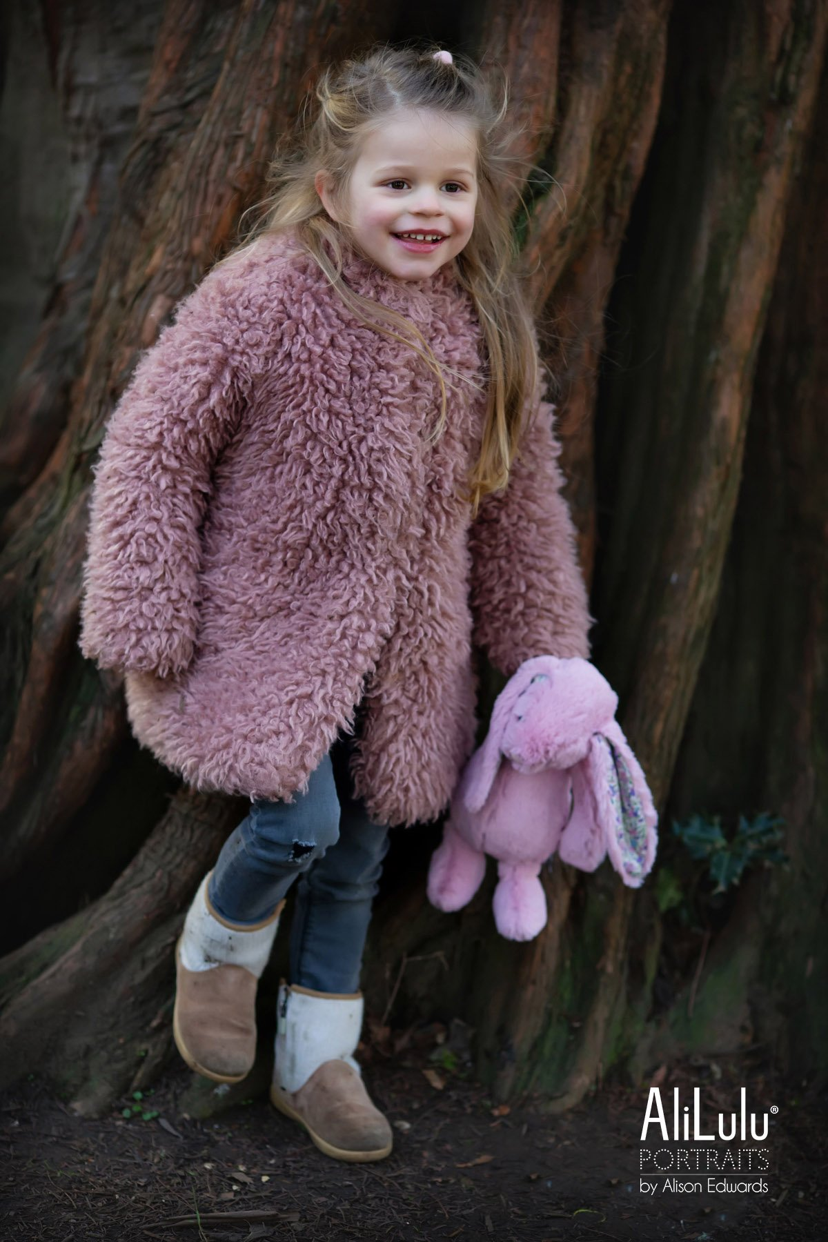 young girl laughing holding bunny teddy in park