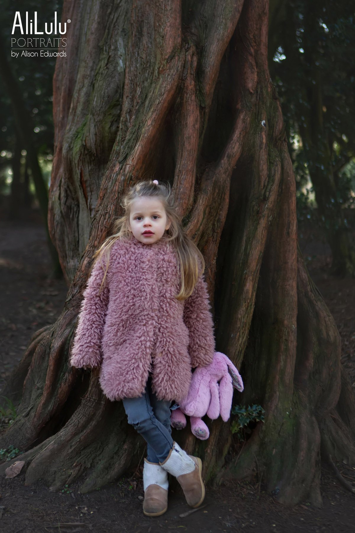 young girl leaning against tree holding bunny teddy
